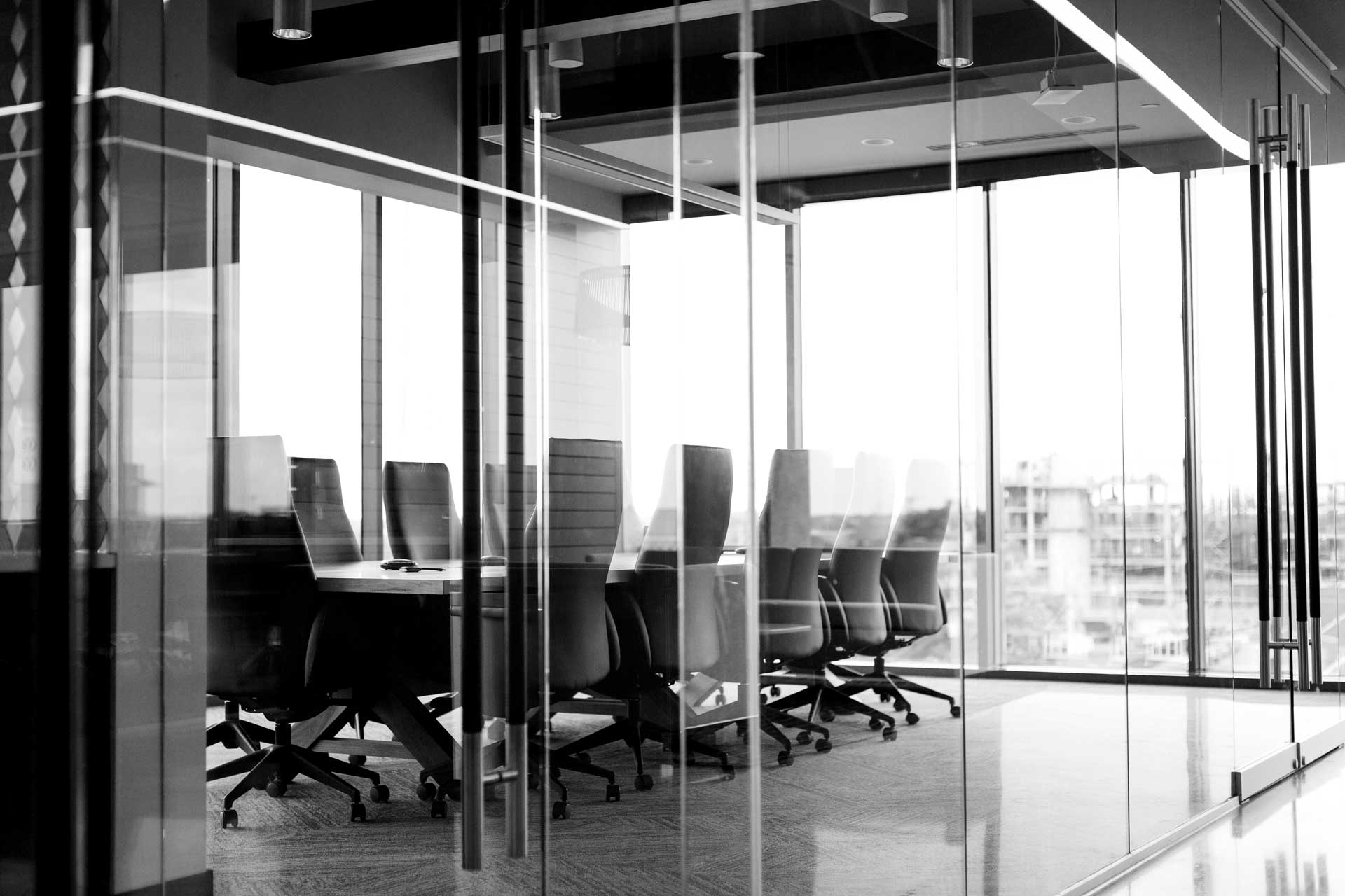Black-and-white photo of conference table and several chairs behind glass doors and glass walls of empty conference room