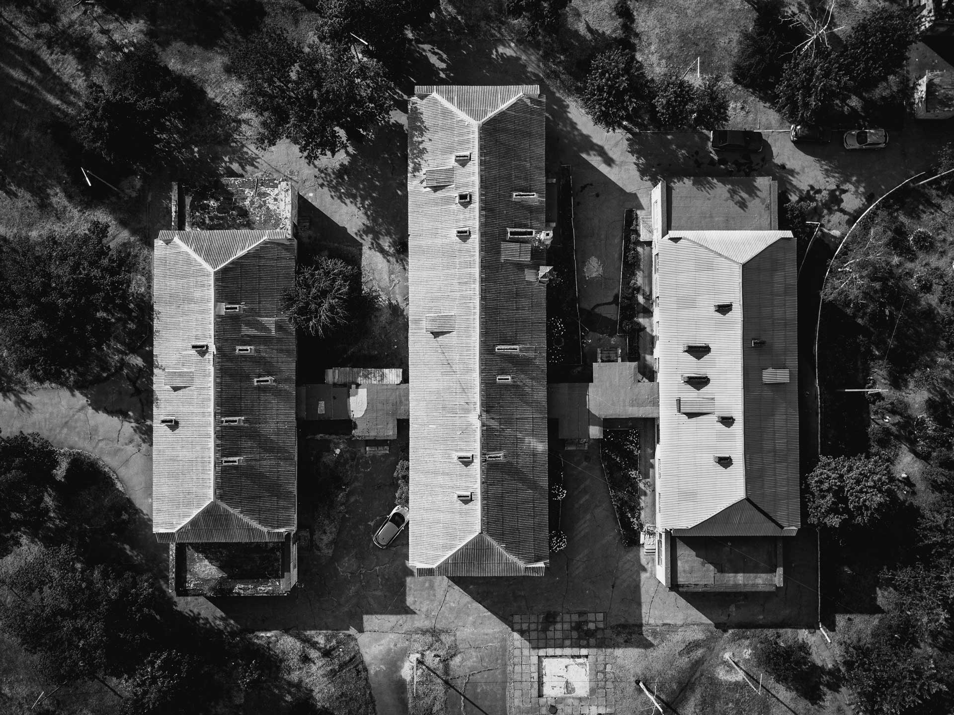 Black-and-white aerial view of the roofs of 3 homes